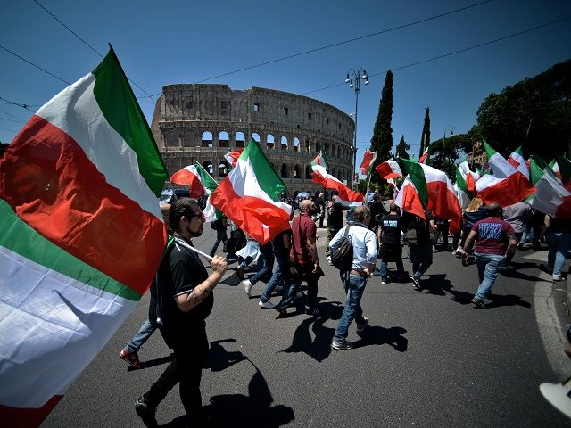 TOPSHOT - Members of Italian far-right political movement CasaPound march with Italian flags near the Colosseum during a demonstration on May 21, 2016 in Rome. AFP PHOTO / FILIPPO MONTEFORTE / AFP / FILIPPO MONTEFORTE (Photo credit should read FILIPPO MONTEFORTE/AFP/Getty Images)