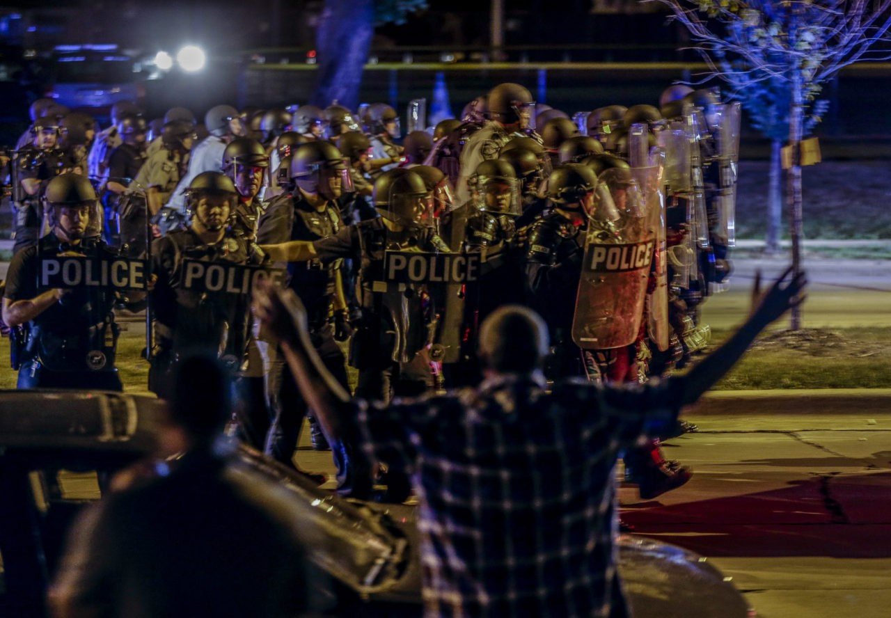 Police move in on a group of protesters throwing rocks at them in Milwaukee, Sunday, Aug. 14, 2016. Police said one person was shot at a Milwaukee protest on Sunday evening and officers used an armored vehicle to retrieve the injured victim during a second night of unrest over the police shooting of a black man, but there was no repeat of widespread destruction of property. (AP Photo/Jeffrey Phelps)