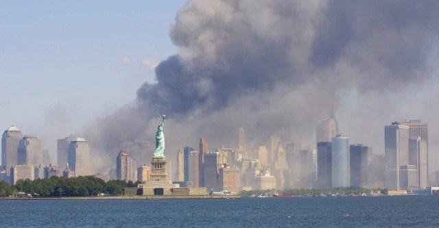 The Statue of Liberty stands as smoke billows from the World Trade Center in New York, Tuesday, Sept 11, 2001 after terrorists crashed two hijacked airliners into the World Trade Center and brought down the twin 110-story towers. (AP Photo/Stuart Ramson)