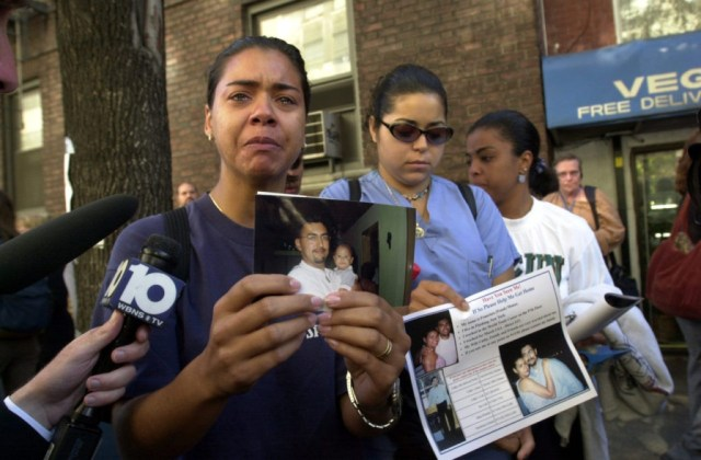 In this September 13, 2001 photograph, a woman poses with a picture of a missing loved one who was last seen at the World Trade Center when it was attacked on September 11, 2001.(AP Photo/Kathy Willens)