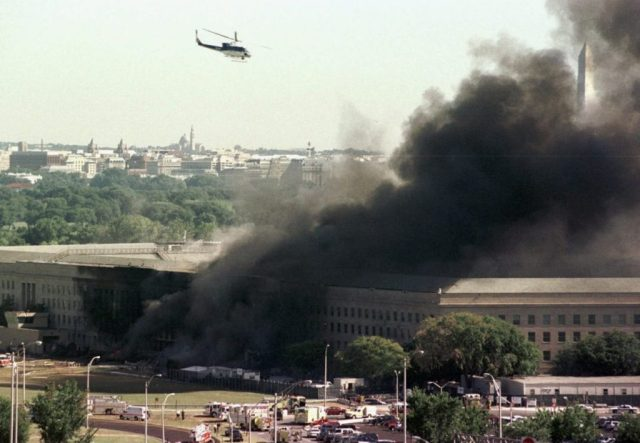 A helicopter flies over the burning Pentagon Tuesday, Sept. 11, 2001. The Washington Monument can be seen at right, through the smoke. The White House roof is visible in the trees of Washington at left. (AP Photo/Tom Horan)