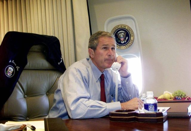 President Bush watches television as he talks on the phone with New York Mayor Rudy Giuliani and Gov. George Pataki aboard Air Force One during a flight following a statement about the terrorist attack on the World Trade Center in New York City, Tuesday, Sept. 11, 2001. (AP Photo/Doug Mills)