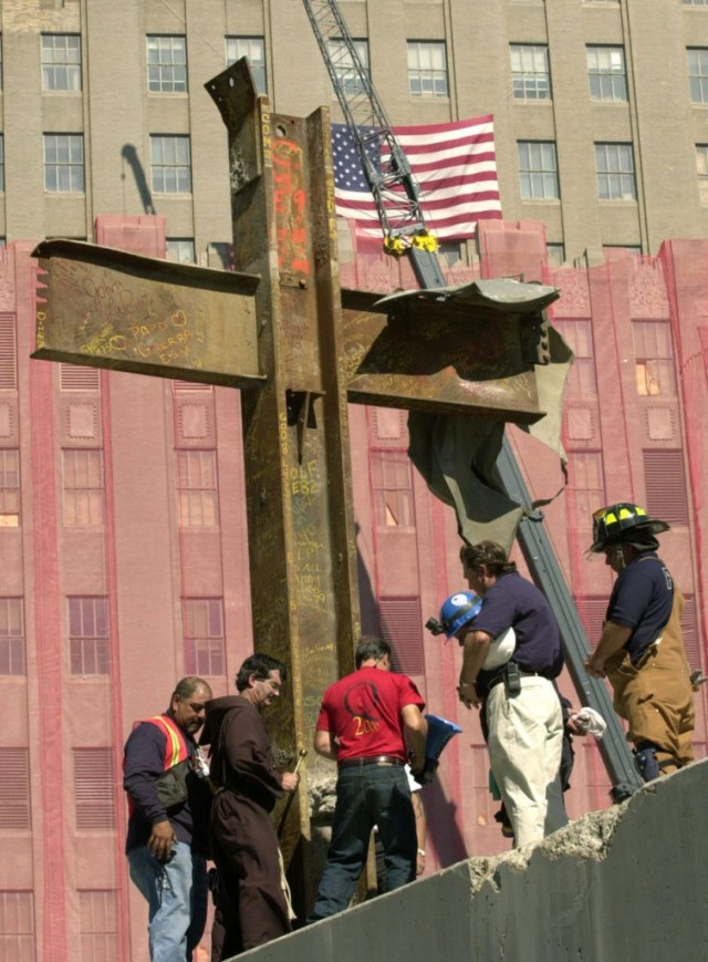 Father Brian Jordan, second from left, blesses, Thursday, Oct. 4, 2001, a cross of steel beams found amidst the rubble of the World Trade Center by a laborer two days after the collapse of the twin towers. The cross was from World Trade tower One, and was found in World Trade building Six and moved to its present location Wednesday. Other rescue and construction workers join Jordan for the ceremony. A protective mesh hangs on the building in the background. (AP Photo/Pool, Kathy Willens)
