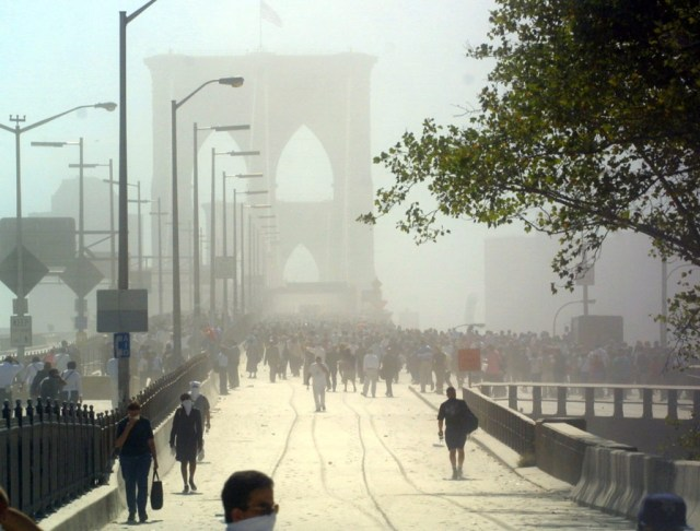 Pedestrians can be seen crossing the Brooklyn Bridge as they flee Manhattan after the collapse of the first World Trade Center Tower 11 September, 2001 in New York. AFP PHOTO Doug KANTER (Photo credit should read DOUG KANTER/AFP/Getty Images)