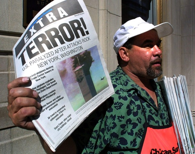 """Newspaper vendor Carlos Mercado sells the """"Extra"""" editon of the Chicago Sun-Times printed 11 September, 2001, after the terrorist attacks on the United States. Two hijacked airplanes crashed into the World Trade Center twin towers in New York while one hijacked plane later crashed at the Pentagon in Washington, DC, with another plane crashing 80 miles outside of Pittsburgh, Pennsylvania. AFP PHOTO/Scott OLSON (Photo credit should read SCOTT OLSON/AFP/Getty Images)"""