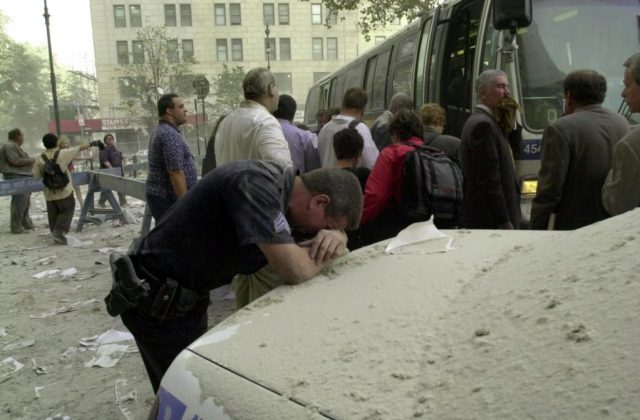 An exausted police officer rests on a car covered in dust near the World Trade Center 11 September 2001 in New York as people board a bus to be evacuated after two hijacked planes crashed into the landmark towers. AFP PHOTO/Stan HONDA / AFP / STAN HONDA (Photo credit should read STAN HONDA/AFP/Getty Images)