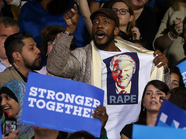 DETROIT, MI - OCTOBER 10:  A protester wears a shirt with an image of former U.S. president Bill Clinton and the word 'rape' as democratic presidential nominee former Secretary of State Hillary Clinton speaks during a campaign rally at Wayne State University on October 10, 2016 in Detroit, Michigan. A day after the second presidential debate in St. Louis, Hillary Clinton is campaigning in Michigan and Ohio.  (Photo by Justin Sullivan/Getty Images)