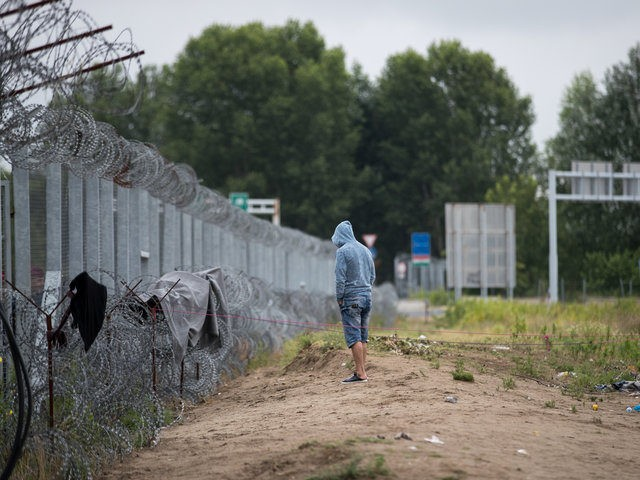 HORGOS, SERBIA - JULY 17: A man stands besides the border fence close to the E75 Horgas border crossing between Serbia and Hungary on July 17, 2016 in Horgos, Serbia. Serbia has announced that it will start joint army and police patrols on its borders with Bulgaria and Macedonia to curb the illegal entry of migrants and people smuggling. The decision comes days after EU member Hungary began sending back to Serbia all illegal migrants caught within five miles of the border fence that was constructed last year. The new rules have led to hundreds of migrants being stranded along the Serbia-Hungary border. (Photo by Matt Cardy/Getty Images)