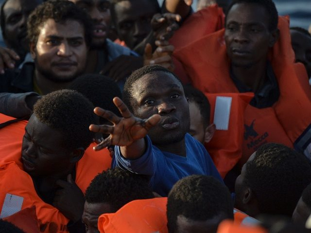 TOPSHOT - Migrants and refugees seated on a rubber boat grab life jackets thrown by members of the crew of the Topaz Responder rescue ship run by Maltese NGO Moas and Italian Red Cross, off the Libyan coast in the  Mediterranean Sea, on November 3, 2016. / AFP / ANDREAS SOLARO        (Photo credit should read ANDREAS SOLARO/AFP/Getty Images)