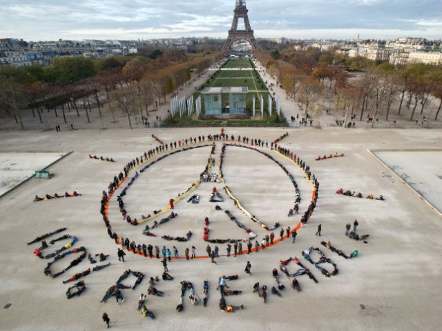 "Environmentalist activists form a human chain representing the peace sign and the spelling out ""100% renewable"", on the side line of the COP21, United Nations Climate Change Conference near the Eiffel Tower in Paris, Sunday, Dec. 6, 2015. Negotiators adopted a draft climate agreement Saturday that was cluttered with brackets and competing options, leaving ministers with the job of untangling key sticking points in what is envisioned to become a lasting, universal pact to fight global warming. (AP Photo/Michel Euler)"