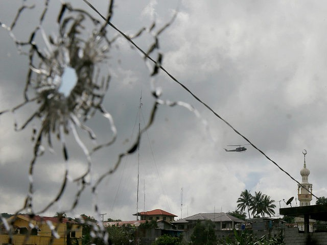 A military helicopter hovering by a mosque is seen through a shattered glass brought about by the fighting between government troops and Muslim militants who continue to hold their ground in some areas of Marawi city for almost a week Monday, May 29, 2017 in southern Philippines. Philippine forces control most of a southern city where militants linked to the Islamic State group launched a bloody siege nearly a week ago, authorities said Monday, as the army launched airstrikes and went house-to-house to crush areas of resistance. (AP Photo/Bullit Marquez)