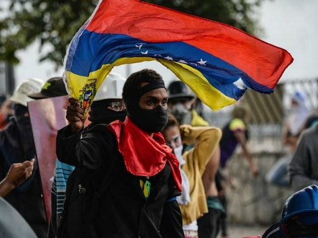 Opposition demonstrators protest in Caracas, on July 26, 2017. Venezuelans blocked off deserted streets Wednesday as a 48-hour opposition-led general strike aimed at thwarting embattled President Nicolas Maduro's controversial plans to rewrite the country's constitution got underway. / AFP PHOTO / FEDERICO PARRA (Photo credit should read FEDERICO PARRA/AFP/Getty Images)