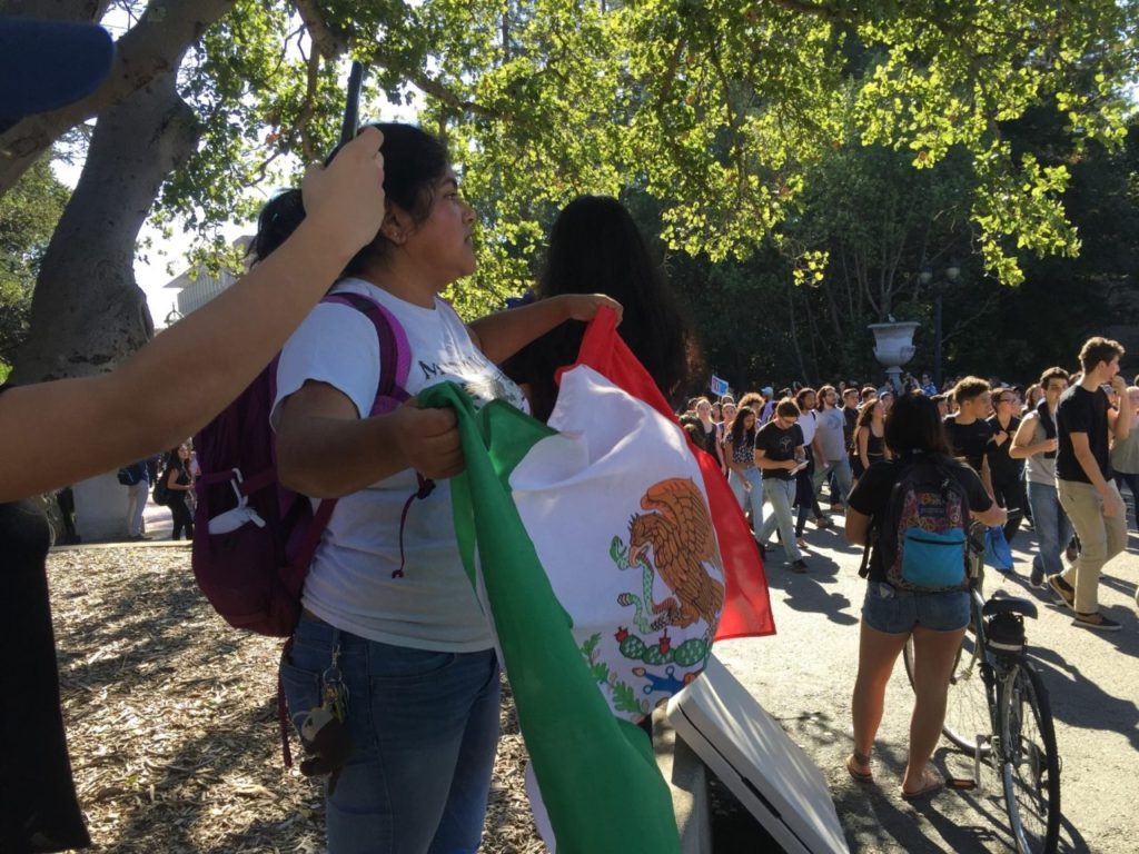 A woman holds a Mexican flag on the campus of UC Berkeley