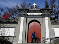 A man peeks through a main entrance gate of the Nantang Catholic Church in Beijing, Wednesday, Dec. 28, 2016. China's head of religious affairs said that Beijing is willing to have constructive dialogue with the Vatican but stressed that Catholics should
