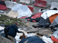 Two men stand next to tents of homeless people, mostly migrants or refugees, by the banks of the Canal Saint Martin, in Paris, on December 24, 2017. / AFP PHOTO / STEPHANE DE SAKUTIN (Photo credit should read STEPHANE DE SAKUTIN/AFP/Getty Images)