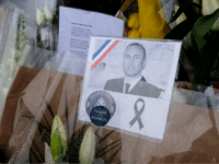 An image Lieutenant-Colonel Arnaud Beltrame is attached to a bouquet of flower laid outside the gates of the gendarmerie of Carcassonne where he worked in southwest France, on March 25, 2018, two days after a man carried out an attack in which he and three other people were killed. Lieutenant-Colonel Arnaud Beltrame, 44, was shot and stabbed after taking the place of a woman whom hostage taker Radouane Lakdim had been using as a human shield during his attack on March 23 on a supermarket in the small town of Trebes several kilometers from Carcassonne. / AFP PHOTO / Eric CABANIS (Photo credit should read ERIC CABANIS/AFP/Getty Images)
