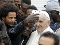 In this Oct. 1, 2017 file photo, Pope Francis poses for selfies with migrants at a regional migrant center, in Bologna, Italy. In a message issued by the Vatican Friday, Nov. 24, 2017, Francis is decrying those whipping up fear of migrants for political gain, and is urging people to view global migration as a peace-building opportunity and not as a threat. (AP Photo/Luca Bruno, files)