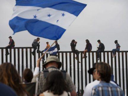 Caravan Migrants climb fence at Mexico/U.S. border.