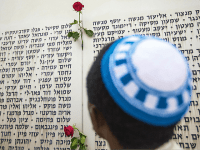 An Israeli man prays in front of a commemorative plaque celebrating fallen soldiers and decorated with roses at the Armored Corps memorial, following a ceremony to mark Remembrance Day (or Memorial Day) on May 5, 2014 at Latrun Junction, near Jerusalem. Israel is marking Remembrance Day to commemorate the fallen Israeli soldiers killed since 1860 and civilians killed in hostile actions since 1948, just before the celebrations of the 66th anniversary of its creation according to the Jewish calendar. AFP PHOTO / JACK GUEZ (Photo credit should read JACK GUEZ/AFP/Getty Images)