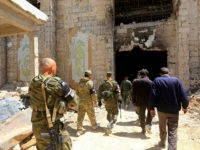 Russian forces patrol damaged buildings in Douma, Syria on the outskirts of Damascus on April 16, 2018 during an organised media tour after the Syrian army declared that all anti-regime forces have left Eastern Ghouta, following a blistering two month offensive on the rebel enclave. The announcement, which represents a key strategic victory for President Bashar al-Assad, came just hours after US-led strikes pounded Syrian government targets in response to a suspected chemical attack on the enclave's main town of Douma. / AFP PHOTO / LOUAI BESHARA (Photo credit should read LOUAI BESHARA/AFP/Getty Images)