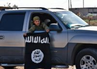 A Syrian pro-government militia member holds a captured Islamic State group flag in June 2017 outside the city of Raqa, which later fell to the Syrian Democratic Forces in October 2017