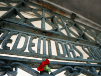 A flower sticks next to the writing 'Jedem das Seine' (literally: To each his own) at the gate of the Buchenwald concentration camp in Weimar, where ceremonies were held 15 April 2007 to mark the 62nd anniversary of the camp's liberation. US army units liberated 21,000 survivors here on 11 April 1945. AFP PHOTO DDP/JENS-ULRICH KOCH GERMANY OUT (Photo credit should read JENS-ULRICH KOCH/AFP/Getty Images)