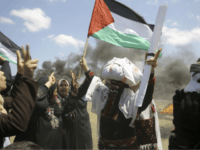 Palestinian women wave national flags and chant slogans near the Israeli border fence, east of Khan Younis, in the Gaza Strip, Monday, May 14, 2018. Thousands of Palestinians are protesting near Gaza's border with Israel, as Israel prepared for the festive inauguration of a new U.S. Embassy in contested Jerusalem. (AP Photo/Adel Hana)