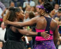 Embrace: Serena and Venus Venus Williams after their match on Friday