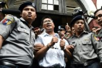 Myanmar journalist Wa Lone of Reuters is escorted by police after being sentenced with his colleague Kyaw Soe Oo to seven years in jail over their reporting on a 2017 massacre of Rohingya Muslims