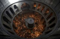 Christian Orthodox worshippers hold up candles during an Easter ceremony in the Church of the Holy Sepulchre in Jerusalem's Old City