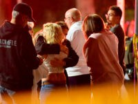 """People comfort each other as they stand near the scene Thursday, Nov. 8, 2018, in Thousand Oaks, Calif., where a gunman opened fire Wednesday inside a country dance bar crowded with hundreds of people on """"college night,"""" wounding multiple people including a deputy who rushed to the scene. (AP Photo/Mark …"""