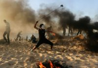 A Palestinian protester hurls stones during a demonstration on the beach near northern Gaza's maritime border with Israel on October 29, 2018