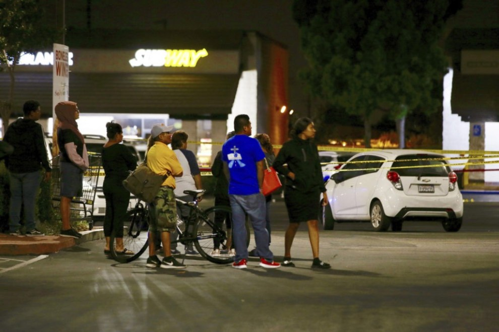 Members of a church group wait behind police lines, fearing they know one person killed by a man stabbing people at a Subway, in Santa Ana, Calif., Wednesday, Aug. 7, 2019. A man killed multiple people and wounded others in a string of robberies and stabbings in California's Orange County before he was arrested, police said Wednesday. (AP Photo/Alex Gallardo)