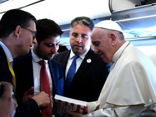 "Pope Francis holds the book "" Comment l'Amerique veut changer le Pape "" ( How the America wants to change the Pope) written by journalist Nicolas Seneze (L) of French newspaper La Croix on board of the plane on the way to Mozambique on September 4,2019. - Pope Francis will …"
