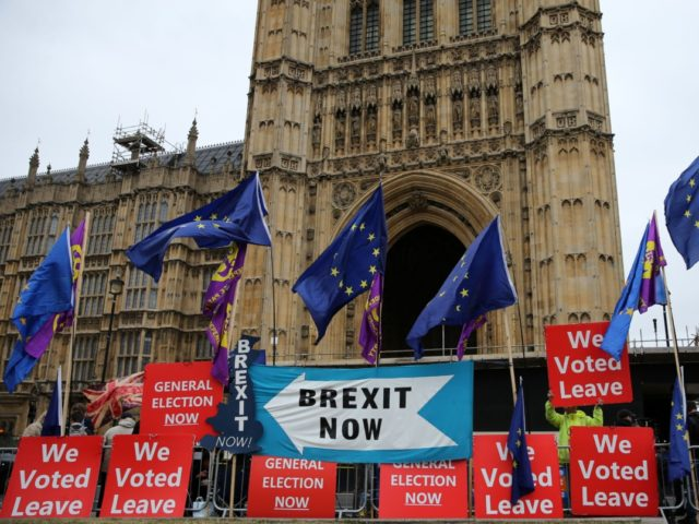 """Pro-Brexit protesters stand with """"We Voted Leave"""" placards among signs calling for """"Brexit Now"""" and EU flags outside the Houses of Parliament in London on September 9, 2019. - British Prime Minister Boris Johnson met his Irish counterpart in Dublin on Monday as he battles to salvage his hardline Brexit …"""