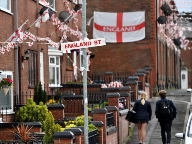 OLDHAM, ENGLAND - JUNE 15: School children walk along Wales Street in Oldham which local residents have re-named England Street and decorated with flags to celebrate the FIFA World Cup Russia 2018 on June 15, 2018 in Oldham, England. England play their first group match against Tunisia on Sunday (Photo …