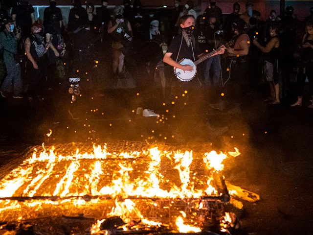 PORTLAND OR - SEPTEMBER 6: Protesters chant in front of a fire near the North police precinct during a protest against racial injustice and police brutality on September 6, 2020 in Portland, Oregon. Sunday marked the 101st consecutive night of protests in Portland. (Photo by Nathan Howard/Getty Images)