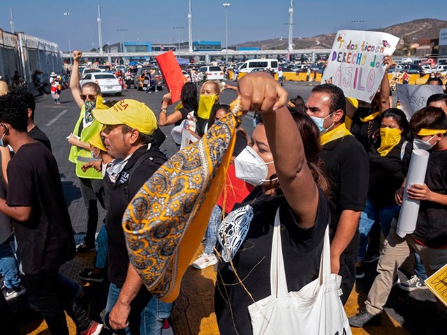 Migrants and human rights activists protest against US and Mexican migration policies at the San Ysidro crossing port, in Tijuana, Baja California state, Mexico, on the border with the US, on October 21, 2020, amid the new coropnavirus pandemic. - With the implementation of the Migrant Protection Protocol (MPP), asylum seekers were forced to remain in Mexico while their migration cases were processed. But, due to the COVID-19 pandemic, US authorities suspended most asylum procedures leaving thousands of migrants stranded along the border. (Photo by Guillermo Arias / AFP) (Photo by GUILLERMO ARIAS/AFP via Getty Images)