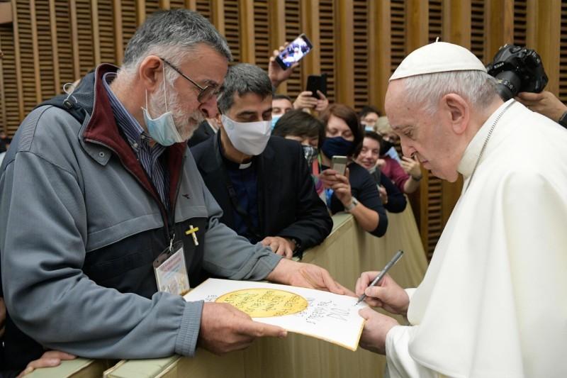 Pope Francis signs memorabilia at General Audience
