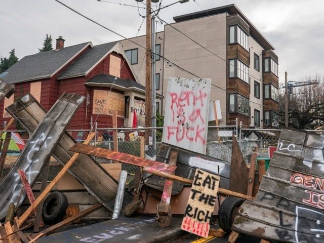 PORTLAND, OR - DECEMBER 10: (EDITOR'S NOTE: Image contains profanity). Barriers surround the Red House, whose residents are up for eviction, on December 10, 2020 in Portland, Oregon. Police and protesters clashed during an attempted eviction Tuesday morning, leading protesters to establish a barricade around the Red House. (Photo by …