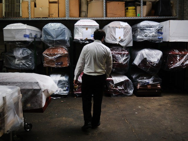 In this file photo, James Harvey tends tends to the inventory of pre-sold caskets at a funeral home on April 29, 2020 in New York City. (Spencer Platt/Getty Images)