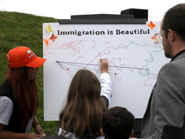 SAN FRANCISCO, CA - AUGUST 17: Attendees put pins on a map of the world during a naturalization ceremony for kids between the ages of 6-12 at Crissy Field near the Golden Gate Bridge on August 17, 2018 in San Francisco, California. Thirty-two children from seven countries were sworn in …