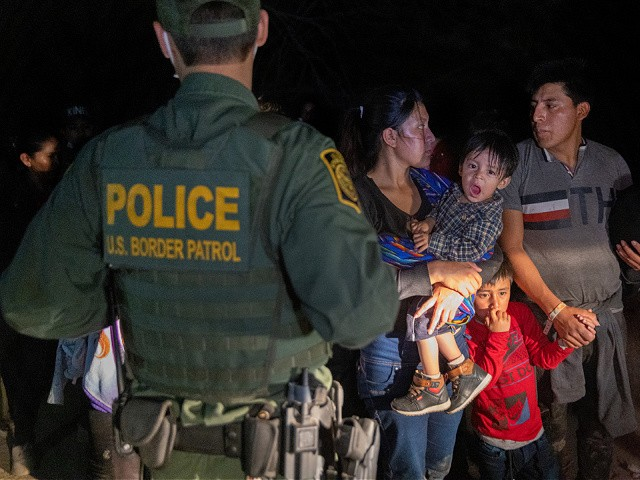 ROMA, TEXAS - APRIL 14: Immigrants wait for a U.S. Border Patrol agent to lead them up from the bank of the Rio Grande after they crossed the U.S.-Mexico border on April 14, 2021 in Roma, Texas. A surge of mostly Central American immigrants crossing into the United States, including record numbers of children, has challenged U.S. immigration agencies along the U.S. southern border. (Photo by John Moore/Getty Images)