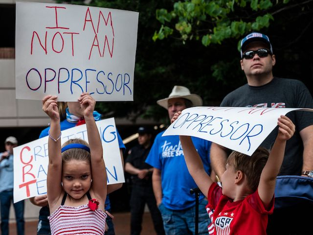"""People hold up signs during a rally against """"critical race theory"""" (CRT) being taught in schools at the Loudoun County Government center in Leesburg, Virginia on June 12, 2021. - """"Are you ready to take back our schools?"""" Republican activist Patti Menders shouted at a rally opposing anti-racism teaching that critics like her say trains white children to see themselves as """"oppressors."""" """"Yes!"""", answered in unison the hundreds of demonstrators gathered this weekend near Washington to fight against """"critical race theory,"""" the latest battleground of America's ongoing culture wars. The term """"critical race theory"""" defines a strand of thought that appeared in American law schools in the late 1970s and which looks at racism as a system, enabled by laws and institutions, rather than at the level of individual prejudices. But critics use it as a catch-all phrase that attacks teachers' efforts to confront dark episodes in American history, including slavery and segregation, as well as to tackle racist stereotypes. (Photo by ANDREW CABALLERO-REYNOLDS / AFP) (Photo by ANDREW CABALLERO-REYNOLDS/AFP via Getty Images)"""