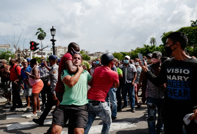 """A man is seized by his neck during a demonstration against the government of Cuban President Miguel Diaz-Canel in Havana, on July 11, 2021. - Thousands of Cubans took part in rare protests Sunday against the communist government, marching through a town chanting """"Down with the dictatorship"""" and """"We want liberty."""" (Photo by ADALBERTO ROQUE / AFP) (Photo by ADALBERTO ROQUE/AFP via Getty Images)"""