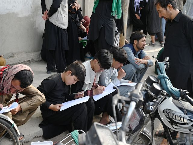 Afghan people fill up their details on a sheet of paper to register their name in order to leave the country in front of the British and Canadian embassy in Kabul on August 19, 2021, after the Taliban's military takeover of Afghanistan. (Wakil Kohsar/AFP via Getty Images)
