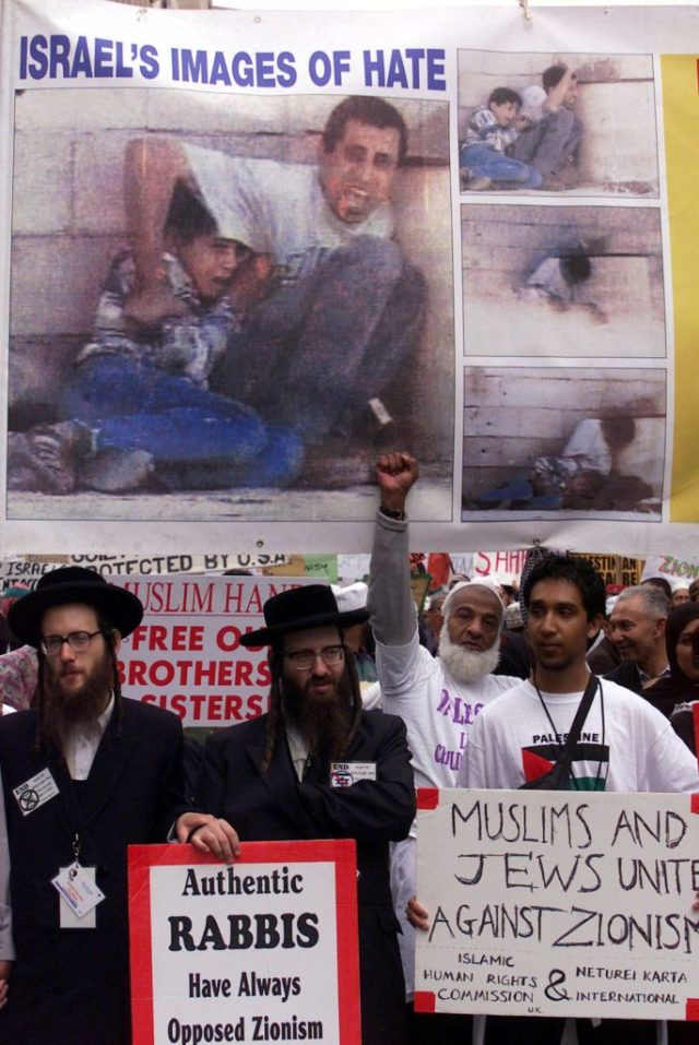 Orthodox Jews and pro-Palestinian supporters participate in a protest march in Durban, South Africa, Friday Aug. 31, 2001 to coincide with the opening of the UN Racism Conference. The series of photographs on the banner show Mohammed Aldura, 12, crouching with his father Jamal Aldura during clashes with Israeli forces in September 2000. Mohammed was fatally shot during the gun battle which was captured on video. (AP Photo/Karel Prinsloo)