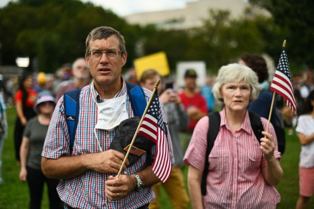 """A couple recites the US Pledge of Allegiance as demonstrators gather for the """"Justice for J6"""" rally in Washington, DC, on September 18, 2021, in support of the pro-Trump rioters who ransacked the US Capitol on January 6, 2021. - Washington was on high alert for the rally with security forces better prepared to avoid a repeat of the January 6 attack on the Capitol. US Capitol police said they have no indication of a specific plot associated with the rally, but warned in a news conference there had been """"some threats of violence,"""" with a counter-rally scheduled to take place nearby. (Photo by ROBERTO SCHMIDT / AFP) (Photo by ROBERTO SCHMIDT/AFP via Getty Images)"""