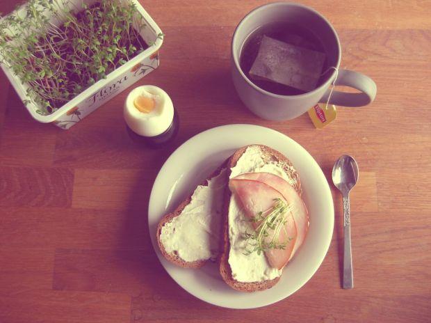 Surdegssmörgåsar med creme cheese, skinka och krasse ett kokt ägg frukost