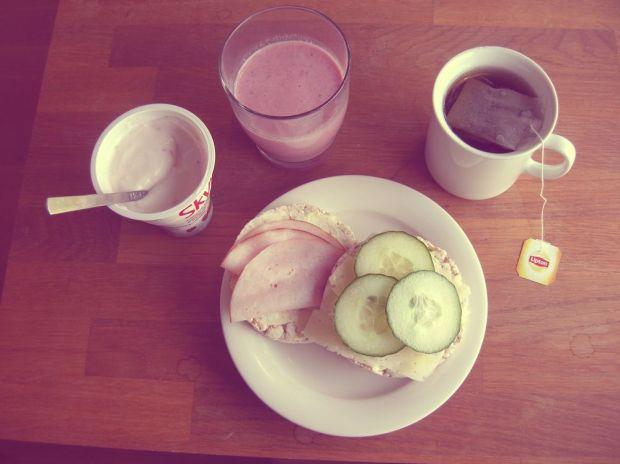 Skyr-yoghurt, en jordgubbssmoothie, en kopp te samt två riskakor